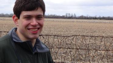 Daniel Lassman in a field where birds peck and dance